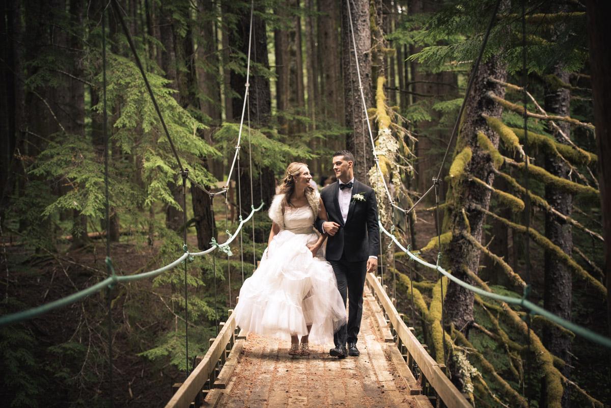 wedding couple, kitimat wedding photographer, wedding couple on bridge,  north coast wedding,  wedding photograph in the trees, outdoor wedding,  wedding on a bridge, wedding couple crosses bridge,